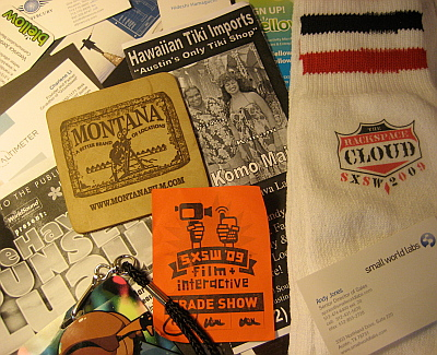 "Artefacts from the event: Rackspace tube socks, Montana film board leather coaster, business cards, BarCamp pass, brochure from ""Austin's only tiki shop"" etc."